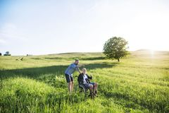 An adult hipster son with senior father in wheelchair on a walk in nature at sunset. An adult hipster son with his senior father in wheelchair on a walk on a Stock Images
