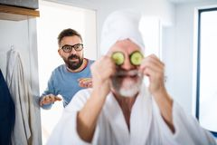 An adult hipster son and senior father in bathroom indoors at home, having fun. A cheerful adult hipster son and senior father in bathroom indoors at home royalty free stock photos
