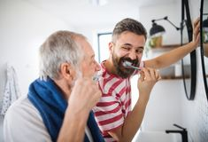 An adult hipster son and senior father brushing teeth indoors at home. An adult hipster son and senior father brushing teeth in the bathroom indoors at home royalty free stock photos
