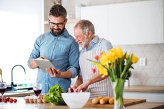 Adult hipster son and senior father indoors in kitchen at home, using tablet. stock photo