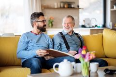 An adult hipster son and senior father sitting on sofa indoors at home, talking. An adult hipster son and senior father with photo album sitting on sofa indoors royalty free stock photography
