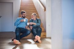 An adult hipster son and senior father sitting on stairs indoors at home, talking. An adult hipster son and senior father with coffee sitting at the bottom of royalty free stock photos