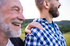 An adult hipster son with senior father on a walk in nature at sunset. An adult hipster son with his senior father on a walk in nature at sunset. Close up royalty free stock photo