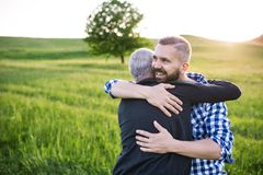 An adult hipster son with senior father on a walk in nature at sunset, hugging. An adult hipster son with his senior father on a walk in nature at sunset royalty free stock photography