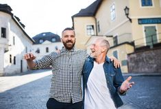 An adult hipster son with senior father on a walk in town. A happy adult hipster son with his senior father in town, walking arm in arm stock photography