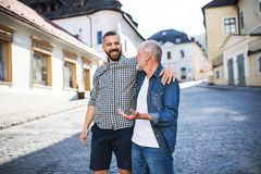 An adult hipster son with senior father on a walk in town. A happy adult hipster son with his senior father in town, walking arm in arm Royalty Free Stock Image