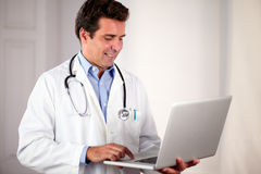 Adult hispanic doctor using his laptop. Portrait of an adult hispanic doctor on white uniform using his laptop while standing and smiling on hospital Stock Photo
