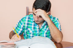 Adult hispanic man studying and writing on a notebook. With a pile of books on his desk Stock Image