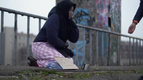 Elderly homeless woman with outstretched hand sits on the bridge in cold windy grey weather asking for alms and help and. Adult homeless woman with outstretched stock video footage