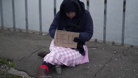 Adult homeless woman sits on the bridge in cold windy grey weather asking for alms and help and writs something on. Elderly homeless woman sits on the bridge in stock video