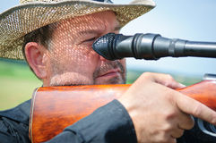 Adult hunter aiming. Portrait of a hunter with a rifle and scope. outdoors. man aims. close-up. curly falls the shadow of the hat. face with stubble Royalty Free Stock Image
