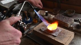Adult jeweler melts gold in a liquid state in a crucible. Craft luxury jewelery