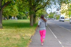 Adult jogger running along street next to park. Adult female jogger with grey sweater running along street lined with vehicles next to park with trees royalty free stock images
