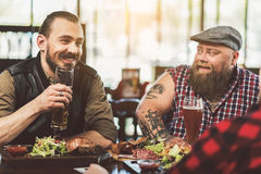 Adult joyful men spending evening in bar Royalty Free Stock Image
