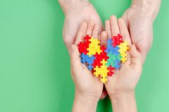 Adult and kid hands holding colorful heart on green background. World autism awareness day concept.  royalty free stock image