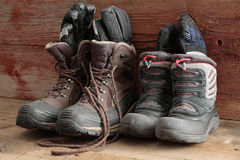 Adult and kids old winter snow boots. With gloves inside them standing ready in a rustic wooden cabin to be worn outdoors in the freezing winter weather Royalty Free Stock Photos
