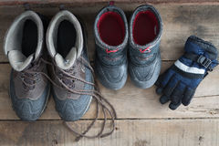 Adult and kids snow boots with gloves. Overhead view of a pair of adult and kids snow boots standing ready on a rustic wooden floor alongside a pair if childs Royalty Free Stock Image