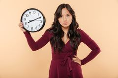 Adult lady with curly long hair holding clock with time after 8. Showing anger with facial expressions, putting hand on waist over beige background Royalty Free Stock Photo
