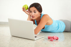 Adult lady laying and surfing the web Royalty Free Stock Images