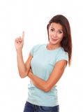 Adult lady pointing up and looking at you Stock Photos