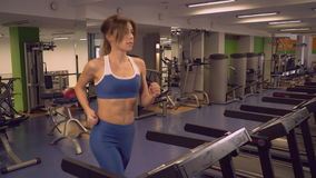 Adult lady running on cardio machines in gym. Female warming up before workout in sport club.Caucasian woman training on treadmill. Attractive runner trains stock video