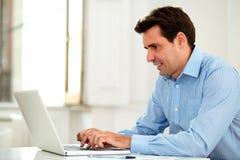 Adult latin enterpreneur using his laptop Royalty Free Stock Image