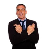 Adult latin man crossing arms and fingers Stock Photo