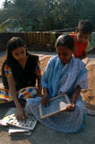 ADULT LITERACY. A young girl is helping an elder woman to understand the alphabets in a rural area in India Royalty Free Stock Photography