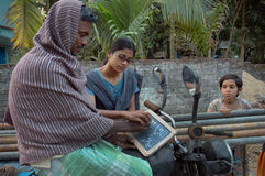 ADULT LITERACY. A young girl is helping a working adult man to understand the alphabets in a rural area in India Stock Photo