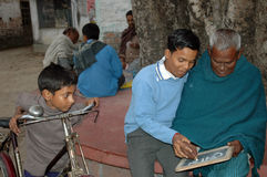 ADULT LITERACY. A young boy is helping a old man to understand the alphabets in a rural area in India Royalty Free Stock Images