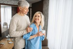 Adult love couple drinks red wine at home. Mature husband and wife have tic dinner, happy family royalty free stock photography