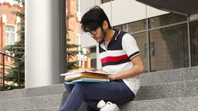 Adult male asian student sitting on stairs and reading book stock footage