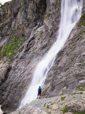 Adult male with a backpack standing lonely on the edge. Of the cliff and looking at the big waterfall Stock Photography