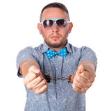 Adult male with beard in a blue bow tie in summer shirt in police handcuffs Royalty Free Stock Images