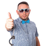 Adult male with beard in a blue bow tie in summer shirt in police handcuffs shows Stock Photos