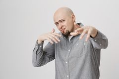 Adult male with beard looking confident at camera and gesturing over white background. Body language and emotions. Concept. Father shows off in front of his son Stock Photo