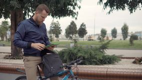 Adult male bicyclist is taking tablet from bag and typing, outdoors. Bearded man is parked his bike and taking tablet from handbag. He is pressing buttons stock video