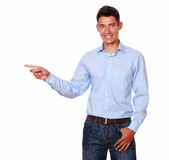 Adult male in blue smiling pointing to his right. Royalty Free Stock Image