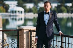 Adult male businessman in a classic black suit with a white shirt and a bow tie. Portrait of the groom waiting for the. Bride on a wedding day in the park on Royalty Free Stock Photos