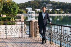 Adult male businessman in a classic black suit with a white shirt and a bow tie. Portrait of the groom waiting for the. Bride on a wedding day in the park on Stock Image