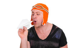 Adult male in a children`s knitted hat pilot playing with a paper plane. The man let a paper airplane. Adult male in a children`s knitted hat pilot playing with royalty free stock images