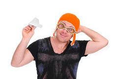 Adult male in a children`s knitted hat pilot playing with a paper plane. The man let a paper airplane. Adult male in a children`s knitted hat pilot playing with royalty free stock image