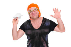 Adult male in a children`s knitted hat pilot playing with a paper plane. The man let a paper airplane. Adult male in a children`s knitted hat pilot playing with royalty free stock photos