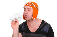 Adult male in a children`s knitted hat pilot playing with a paper plane. The man let a paper airplane. Stock Image