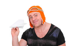 Adult male in a children`s knitted hat pilot playing with a paper plane. The man let a paper airplane. Stock Photos