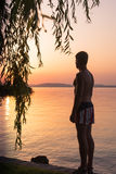 Adult male concerns sunset on the lake. In summer Stock Photo