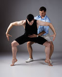 Adult male dancer. Wearing a black shirt and pants and ballet dance instructor. Teacher is assisting the student Stock Photo