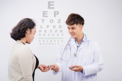 Adult male doctor examing adult female patient Stock Images
