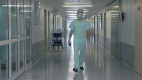 Adult male doctor is passing by the hospital hall. 4K stock video