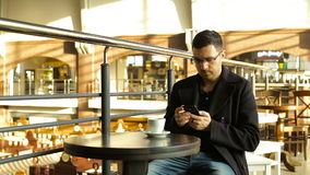 Adult male drinking coffee with a phone in his hand in cafes stock footage
